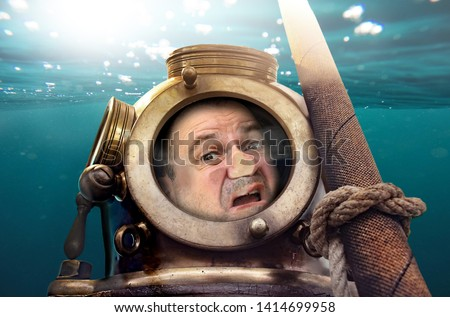 Portrait of man in old diving suit and helmet under water. Funny diver in retro equipment with face crushed on glass. #1414699958