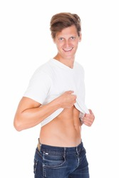 Portrait Of Man Lifting His T-shirt Showing Abs