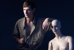Portrait of man next to a mannequin. Man with glasses in his hands on a dark background. Man next to a humanoid cyborg. Human-like cyborg.as a symbol of artificial intelligence. Human leans on cyborg