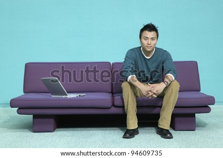 Portrait of man on couch with laptop