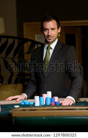 Portrait of man standing at casino table with gambling chips