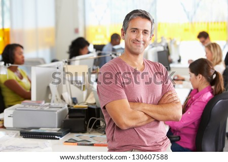Portrait Of Man Standing In Busy Creative Office