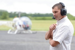 portrait of man standing in front of helicopter