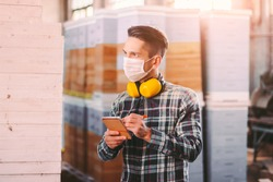 Portrait of man supervisor in medical face mask and protective headphones checking wood material inventory at storage. Young warehouse worker inspecting, counting woodwork stock. COVID-19 quarantine