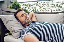 Portrait of man taking nap on apartment terrace