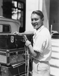 Portrait of man tying down luggage