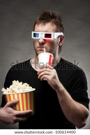 Portrait of man watching 3D movie, drinking cola and holding bucket of popcorn