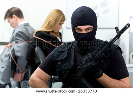 Portrait of man wearing black balaclava with gun looking at camera on background of scared business people