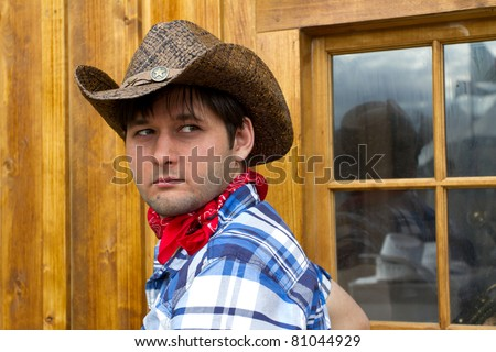 Portrait of man wearing cowboy hat, silk scarf, and checked shirt. Photo is taken in Calgary during Stampede
