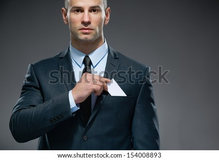 Portrait of man who pulls out white card from the pocket of business suit, copyspace