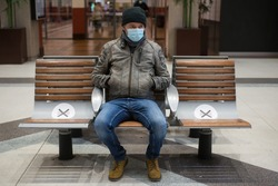 Portrait of man with a medical mask sitting on bench with social distancing symbols in the train station