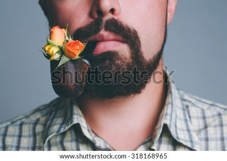 Portrait of man with beard and smoke pipe with rose flowers inside it, focus on flowers