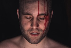 Portrait of man with blood on his face on dark background.
