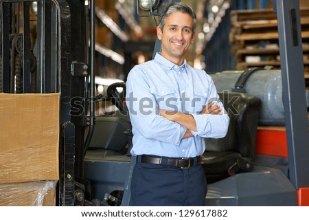 Portrait Of Man With Fork Lift Truck In Warehouse