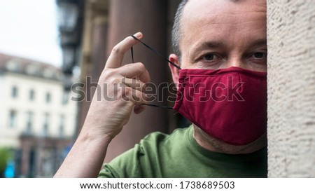 Portrait of man  with homemade red fabric mask to protect against the coronavirus pandemic in outdoor Foto d'archivio ©