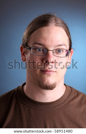 portrait of man with long hair and eyeglass - stock photo
