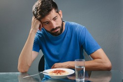 Portrait of man with no appetite in front of the meal. Concept of loss of appetite