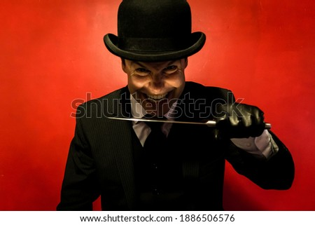 Portrait of Maniacal Man in Dark Suit Holding a Sharp Knife and Grinning Sadistically. Concept of Horror Movie Murderer. Dark Stock Photo. Copy Space for Fear. Сток-фото ©