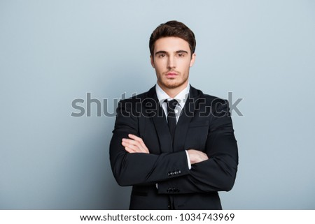Portrait of manly,  brutal, masculinity, attractive director in black formal wear, having arms crossed, standing over gray background
