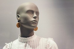 Portrait of mannequin. Woman profile face in store window. Isolated bald dummy. Shopping, beauty or feminine concept. Copy space for text