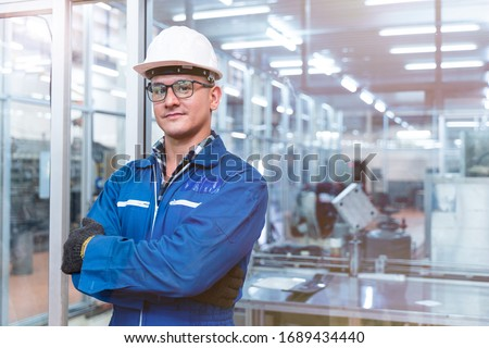 Portrait of manual man worker is standing with confident with blue working suite dress and safety helmet in front the glass wall of high technology clean industry factory.