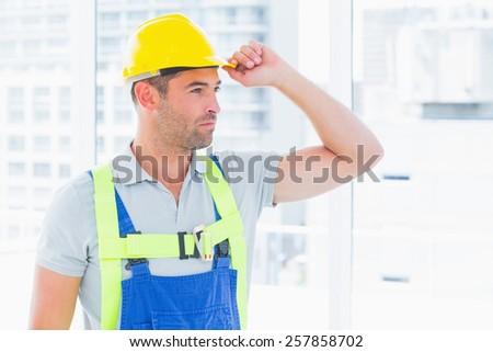Portrait of manual worker wearing yellow hard hat in bright office