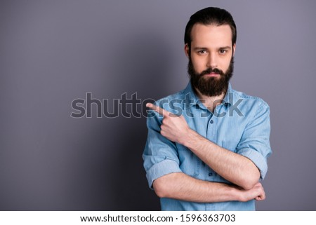 Portrait of masculine brutal bearded guy point index finger copy space indicate promo adverts present advertisements suggest select wear casual style outfit isolated grey color background
