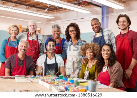 Portrait Of Mature Adults Attending Art Class In Community Centre With Teacher