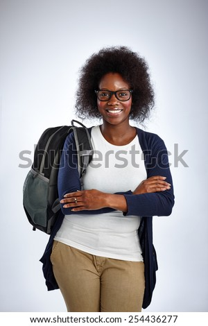 Portrait of mature african woman with backpack standing with her arms crossed over white background
