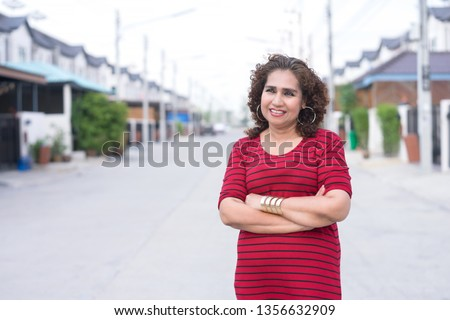 Portrait of mature asian woman looking to something happily on blurry background.