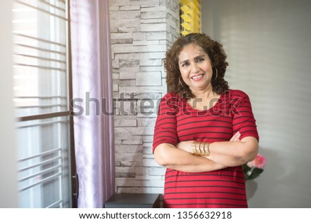 Portrait of mature asian woman smile to the camera in her house with some light from window.