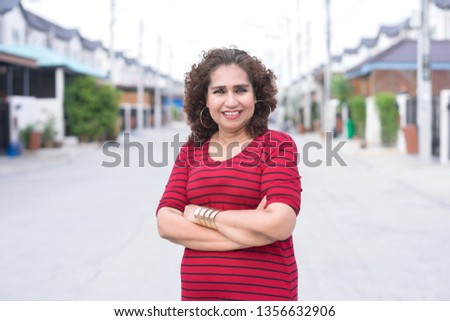 Portrait of mature asian woman smile to the camera.She standing on her village road background.