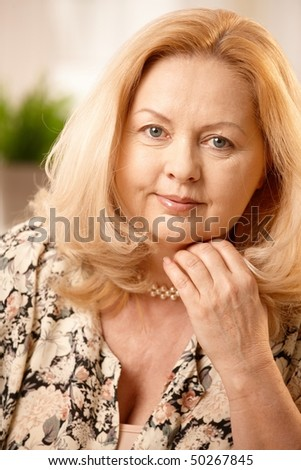 stock photo : Portrait of mature blonde woman smiling at camera, ...