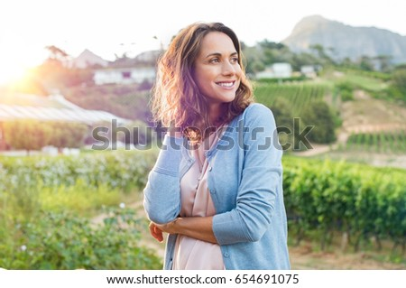 Shutterstock Portrait of mature brunette woman relaxing at park and looking away. Happy woman relaxing outdoor at sunset. Smiling mature woman thinking.