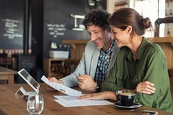 Portrait of mature business man and casual businesswoman sitting in cafe and discussing sales graph. Group of two middle aged coworkers working comparing forecasting graphics. Happy businesspeople.