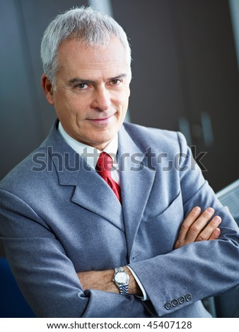 portrait of mature business man with arms folded, looking at camera. Copy space