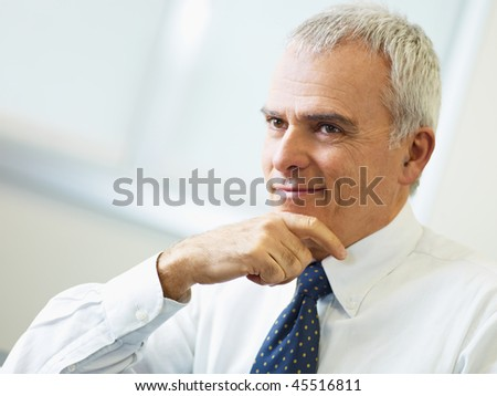 portrait of mature business man with hand on chin, looking away. Copy space - stock photo