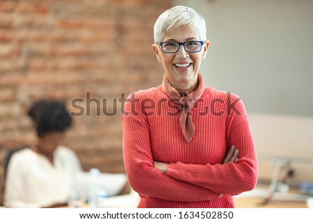 Portrait of mature business woman standing at office.Pretty older business woman, successful confidence with arms crossed in financial building. Mature female in office with team meeting in background