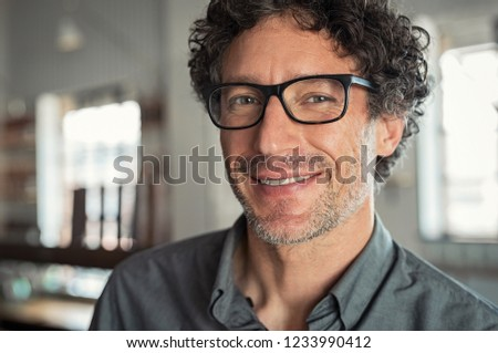 Portrait of mature businessman wearing glasses. Closeup face of smiling proud business man wearing eyeglasses and looking at camera. Satisfied senior man wearing spectacles indoor.