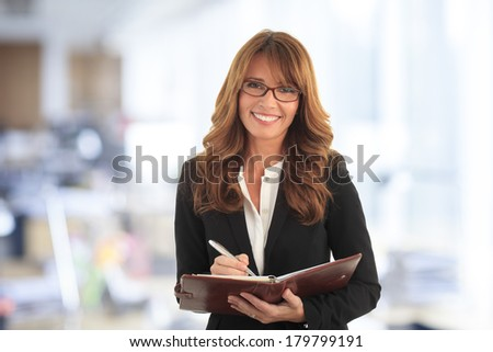 Portrait of mature businesswoman standing and making a list in her office.