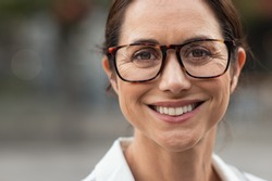 Portrait of mature businesswoman wearing eyeglasses and looking at camera. Close up face of cheerful woman with spectacles smiling outdoor. Confident beautiful entrepreneur wearing specs.
