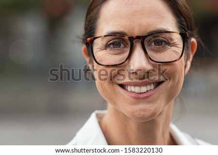Portrait of mature businesswoman wearing eyeglasses and looking at camera. Close up face of cheerful woman with spectacles smiling outdoor. Confident beautiful entrepreneur wearing specs. Stock photo ©