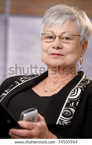 Portrait of mature businesswoman with cellphone looking at camera, smiling.?