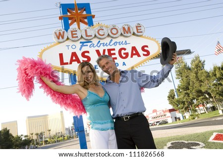 Portrait of mature couple in front of 'Las Vegas' sign