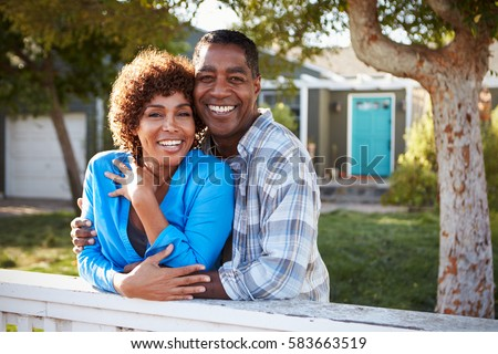 Portrait Of Mature Couple Looking Over Back Yard Fence