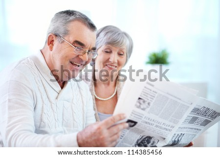 Portrait of mature couple reading newspaper together