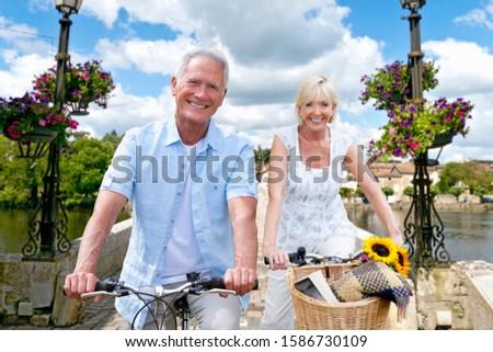 Portrait Of Mature Couple Riding Cycle Over Bridge