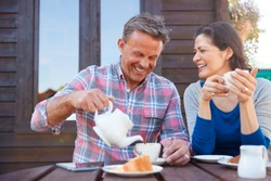 Portrait Of Mature Couple Sitting On Bench In Cafe Whilst Visiting Garden Center