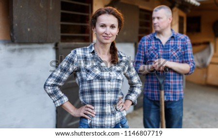 Portrait of mature couple standing with tools at farm with pet outdoor