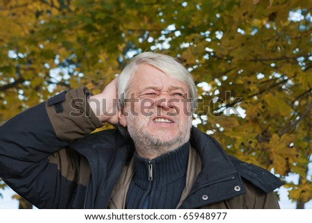 Portrait of mature emotional man with grey hair in autumn day.